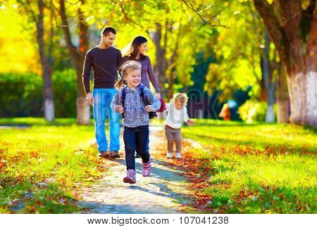 Happy Young Girl Running In Autumn Park With Her Family On Background