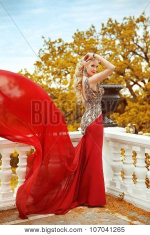 Beautiful Gorgeous Sexy Woman In Elegant Mermaid Red Dress With Blowing On The Balcony Over Autumn P