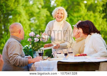 Woman serving ring cake at birthday party with senior people in a garden