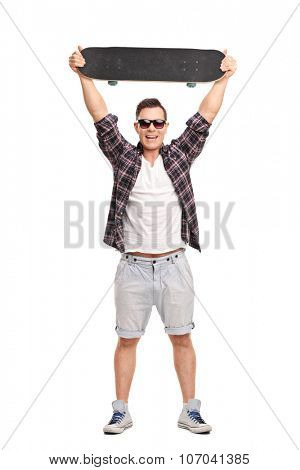 Full length portrait of a young male skater holding a skateboard above his head and looking at the camera isolated on white background