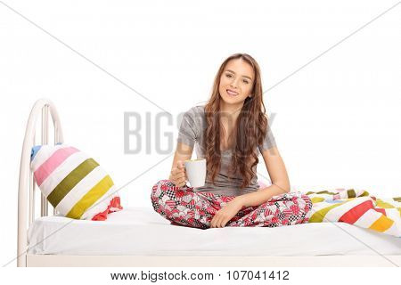 Young brunette woman in pajamas sitting on bed and holding a cup of coffee isolated on white background