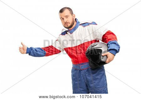 Studio shot of a young man in a racer suit holding a helmet and hitchhiking with his thumb isolated on white background