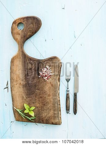 Kitchen-ware set. Walnut wooden chopping board, knife, fork, spices and herbs on a light blue backgr