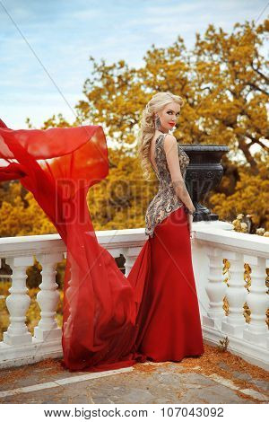 Beautiful Gorgeous Woman Model In Elegant Mermaid Red Dress With Blowing On The Balcony In Autumn Pa