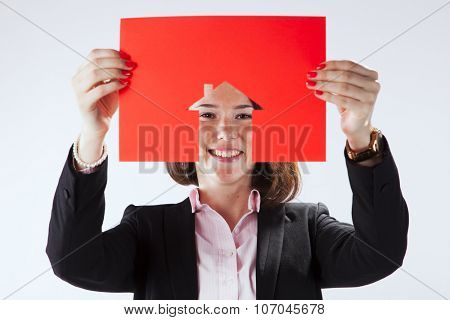 Woman face behind a red cut out paper with a house shape