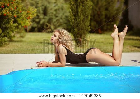 Bikini Model. Beautiful Sexy Woman With Wavy Hair In Black Bikini Posing And Sunbathing By The Blue