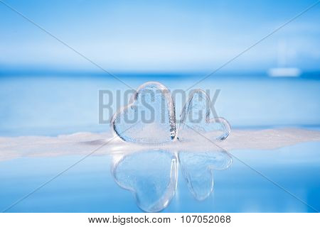 clear glass hearts in foam on wet white glass with reflection