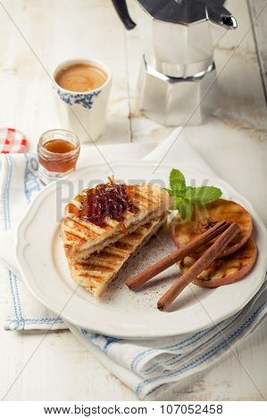 French toasts with orange marmalade, grilled apples and cinnamon sticks.