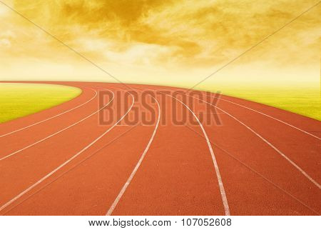 Outdoor Racetrack With Green Grass At Sunset