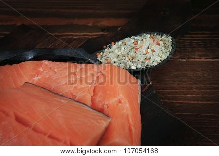 fresh raw salmon fillet served with lemon and white wine in wineglass, bottle, on dark plate over vintage wood table with handmade cutlery knife and spice on spoon