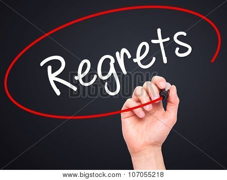 Man Hand writing Regrets with black marker on visual screen.
