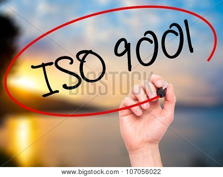 Man Hand writing Iso 9001 with black marker on visual screen.