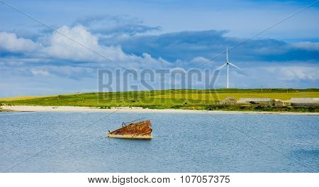 Old Rusted Sunken Boat  And Eolic Fan In Background