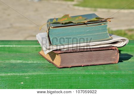 Books And Newspapers On Wooden Bench