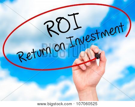 Man Hand writing ROI Return on Investment with black marker on visual screen.