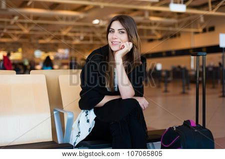 Woman waiting in terminal while waiting for her flight.