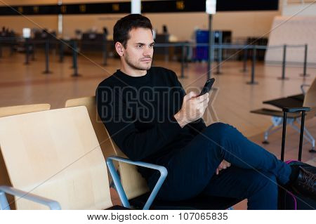 Man with his mobile phone while sitting in the hall of the airport.