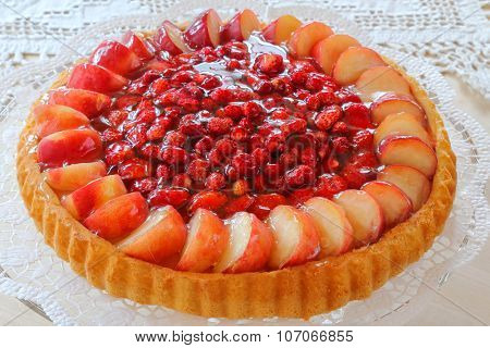 The classic Biskuit or German Biscuit, known as Sponge Cake decorated with fresh wild strawberries, garden strawberries, and peach