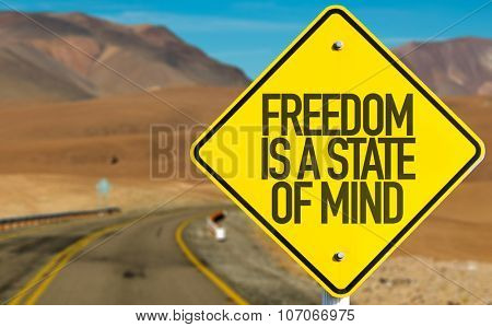 Freedom Is a State of Mind sign on desert road