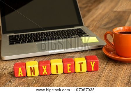 Anxiety written on a wooden cube in front of a laptop