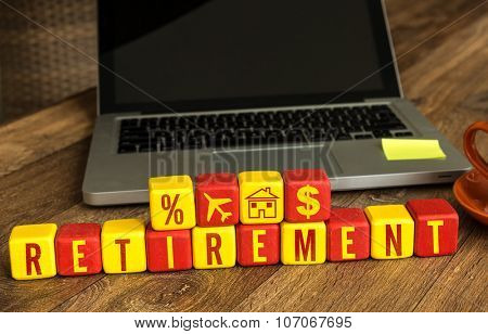 Retirement written on a wooden cube in front of a laptop