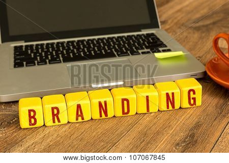 Branding written on a wooden cube in front of a laptop
