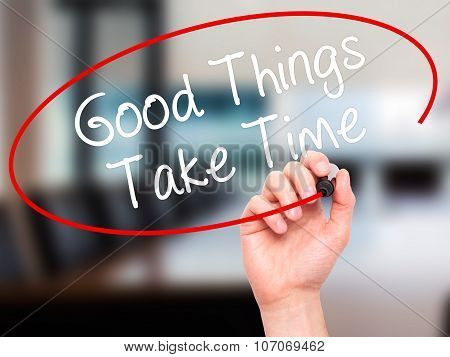 Man Hand writing Good Things Take Time with black marker on visual screen