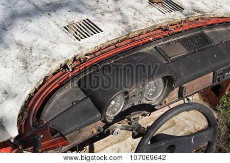 Steering Wheel And Rusty Speedometer On Vintage Car Dashboard
