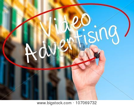 Man Hand writing Video Advertising with black marker on visual screen.
