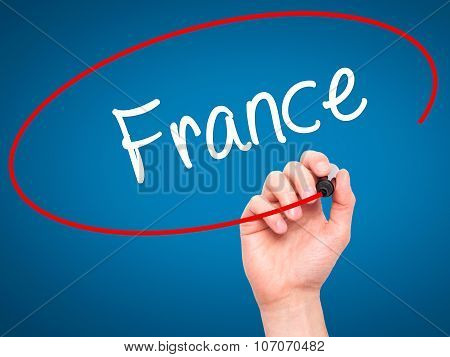 Man Hand writing France with black marker on visual screen.