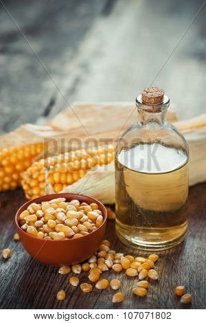 Corn Essential Oil Bottle, Seeds In Bowl And Two Corncobs On Kitchen Table