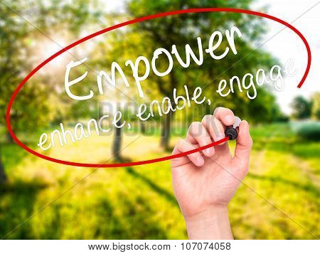 Man Hand writing Empower enhance, enable, engage with black marker on visual screen.