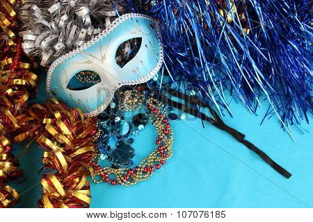 Blue carnival mask on a blue background with festive decorations