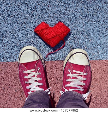 high-angle shot of a heart-shaped coil of red yarn and the feet of a man wearing red sneakers stepping on the asphalt
