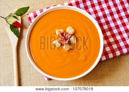high-angle shot of a bowl with spanish salmorejo, a typical cold soup made with tomato and bread, topped with serrano ham and croutons, on a set table