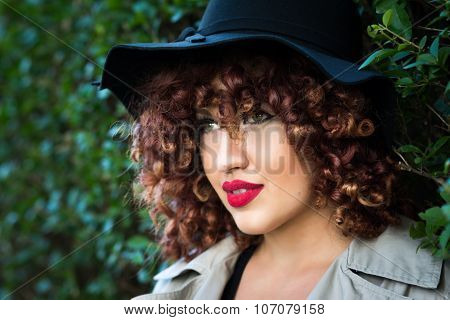 Beautiful young woman with curly red hair and fedora hat