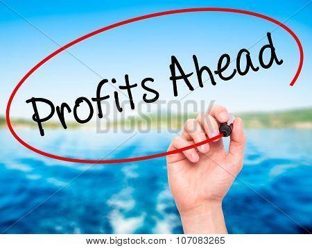 Man Hand writing Profits Ahead with black marker on visual screen.