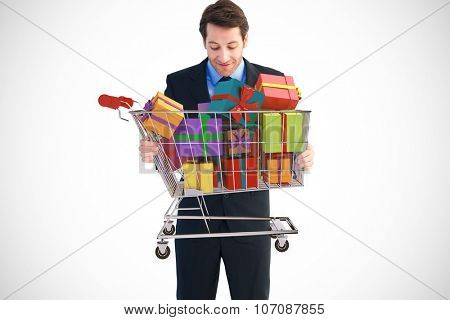 Businessman holding something with his hands against trolley full of gifts