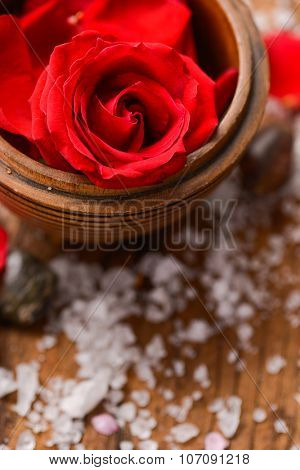 Red roses in bowl with pile of salt ,stones on old wooden board