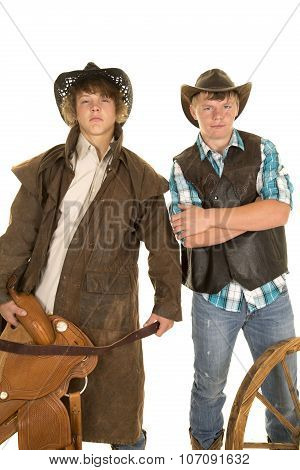 Two Young Cowboys With Saddle And Wagon Wheel