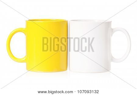 Yellow and white mugs empty blank for coffee or tea isolated on white background