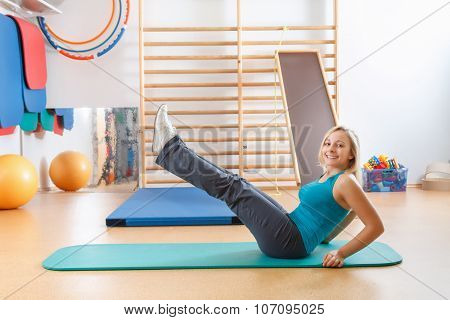 Young woman doing sport exercises at the gym.