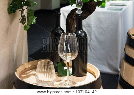 The Goblet And Wine Bottles On Wooden Barrel.