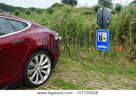 Red Tesla Model S being charged