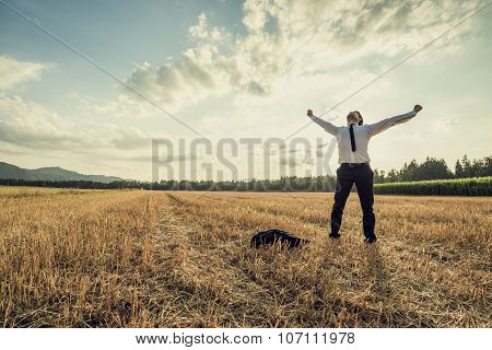 Successful Businessman Standing Victoriously In The Middle Of Field