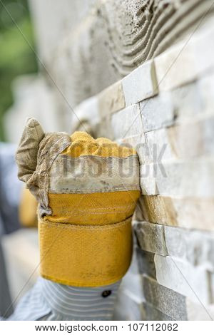 Male Hand In Protective Work Glove Making A Fist While Pressing An Ornamental Tile Into A Glue