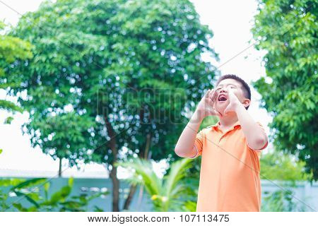 Portrait Of Asian Child Yelling, Screaming, Shouting, Hand On His Mouth