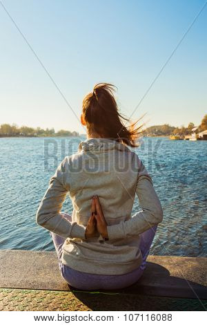 young woman practice yoga by the lake sunny autumn day, back view