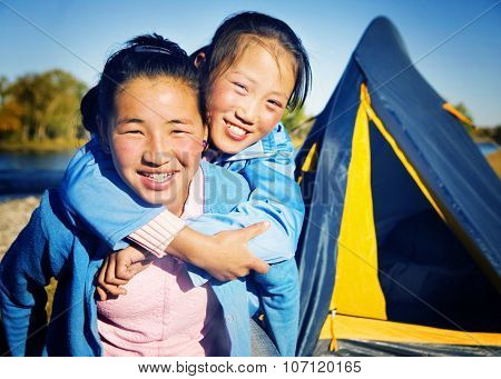 Happy Mongolian Girls Playing Piggyback At Campsite Concept