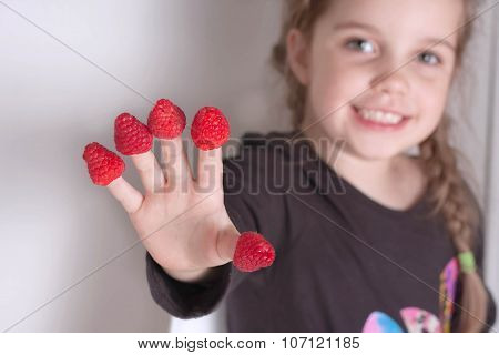 little girl showing off her hand with raspberries on each finger